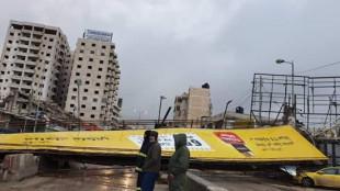 سقوط لوحة اعلانية في وسط شارع قلنديا