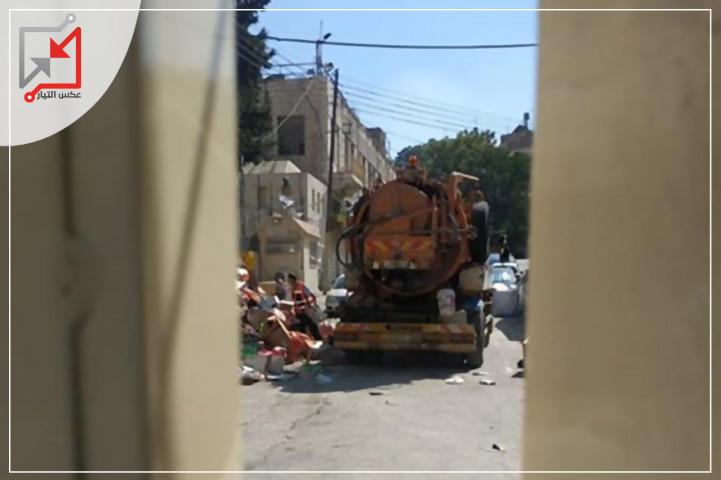 سيارة نضح مياه الصرف الصحي التابعة لبلدية الخليل تقوم بتنظيف وتسليك المجاري أمام مستوطنة بيت رومانو