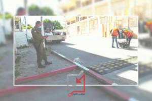 ضابط من الادارة المدنية الاسرائيلية برفقة عمال بلدية الخليل أثناء قيام البلدية يتركيب مطبات